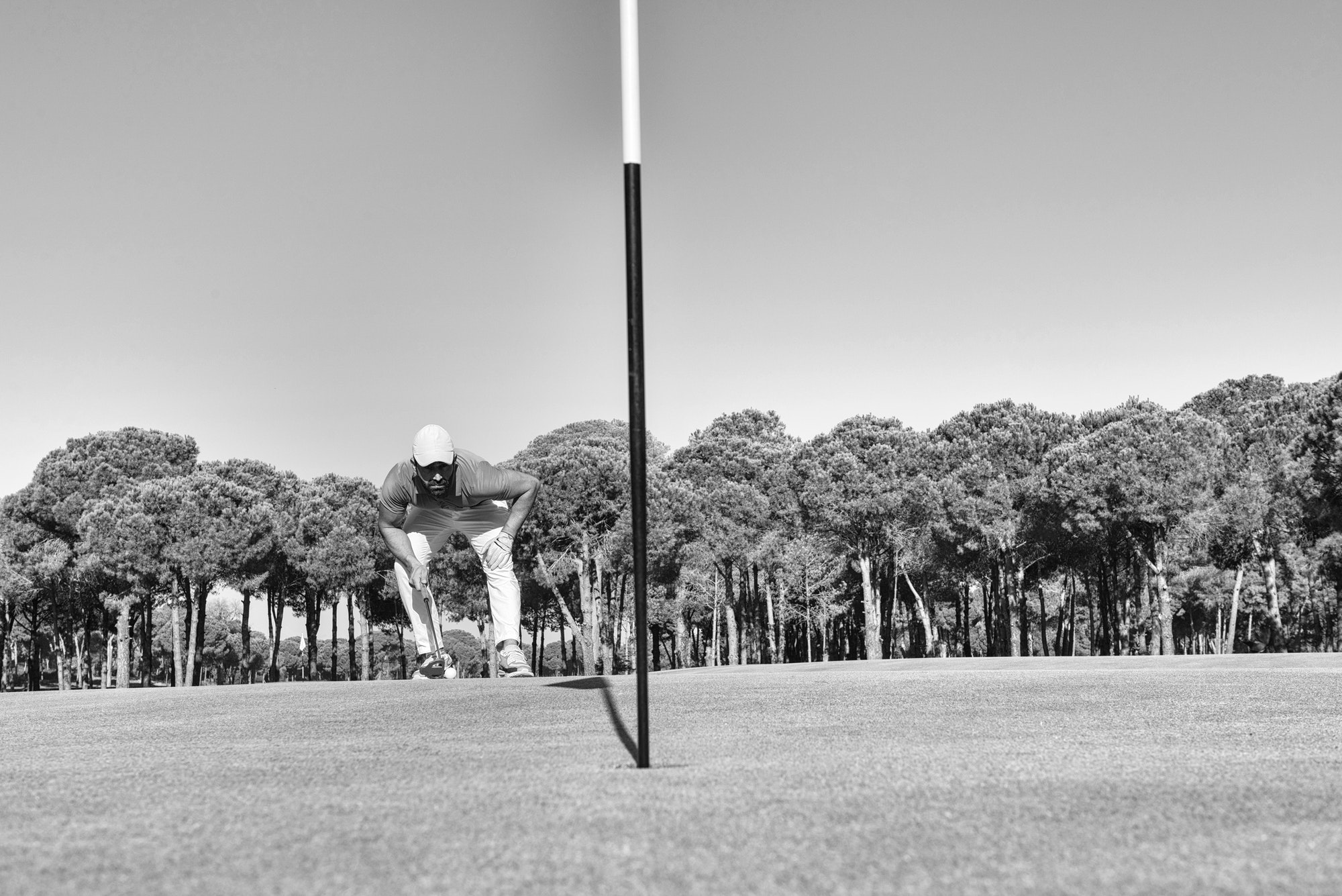 Putting with the flagstick. In or out? And why?